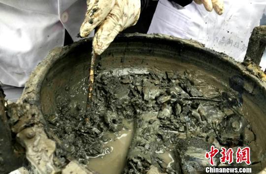 """图为考古专家对挖掘出的大鼎内的""""肉汤""""。 河南省文物考古研究院供图"""