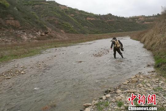 图为童金南教授趟水过河前往剖面。 田力 摄